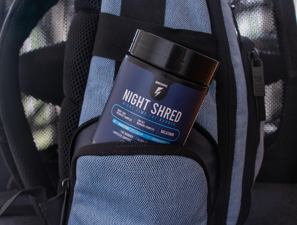Navy supplement bottle sticking out of the side of a small pouch of a backpack.