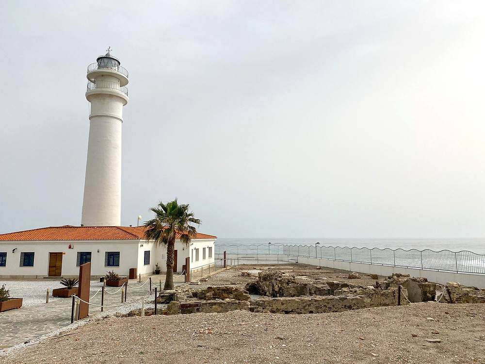 White lighthouse rising out of a building with an orange roof along the coast. There's a Roman ruin on the ground next to it.