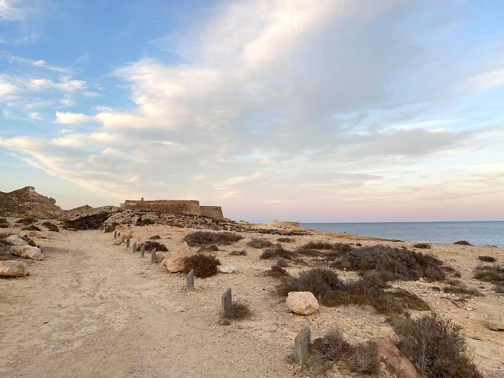Castillo de San Ramón sitting on a hill next to Playa el Playazo in Almeria, Spain
