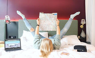 Hotel bed with Krista the Explorer holding a map with legs in the air.