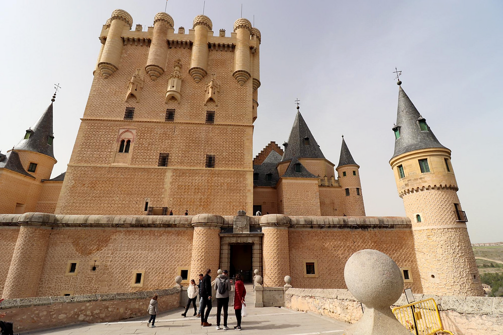 Large medieval castle made of yellow brick and blue pointed towers.