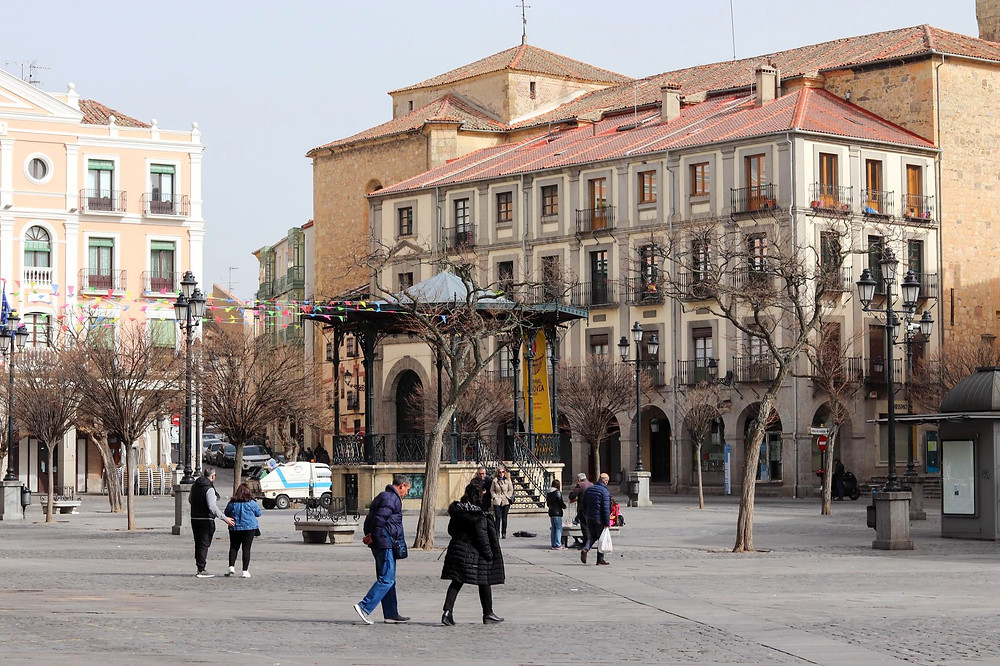 Main plaza in Segovia with colourful buildings and trees lining the outer parts of it.