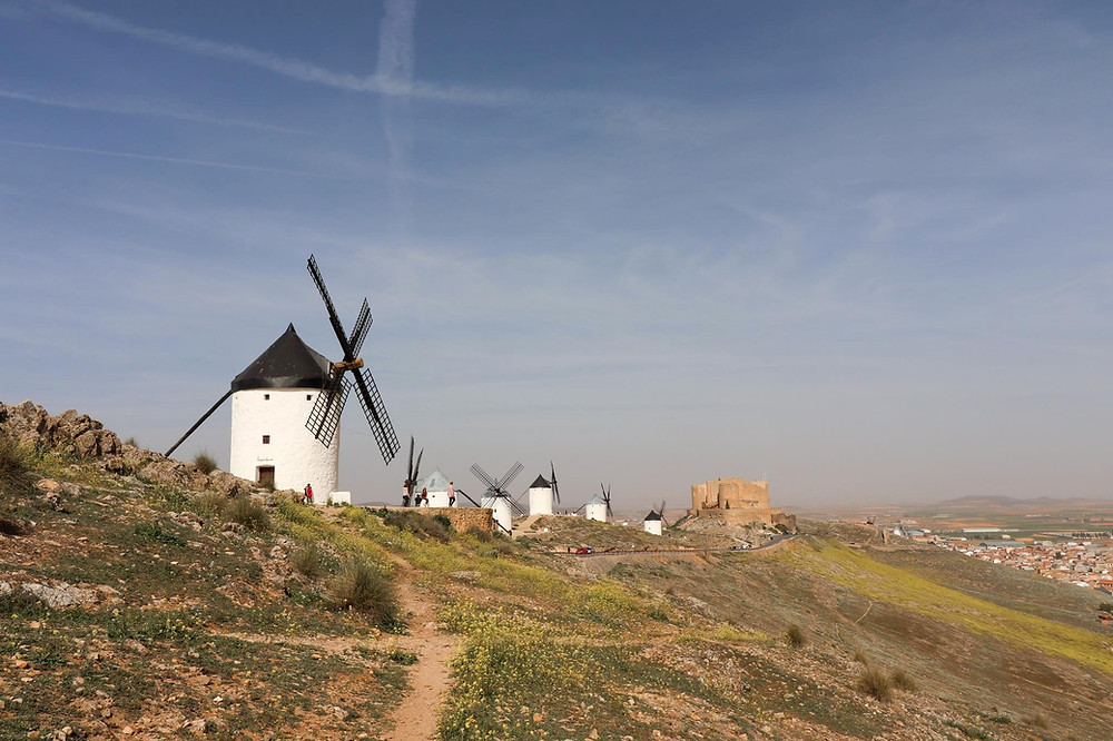 View of 6 white painted windmills in a line and a castle at the end of the line, all on a hill.