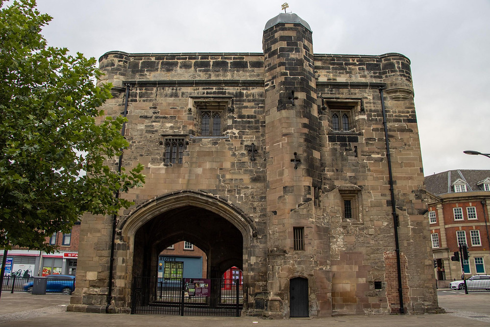 Medieval entry gate standing by itself in the middle of a pedestrian area with a road behind it.
