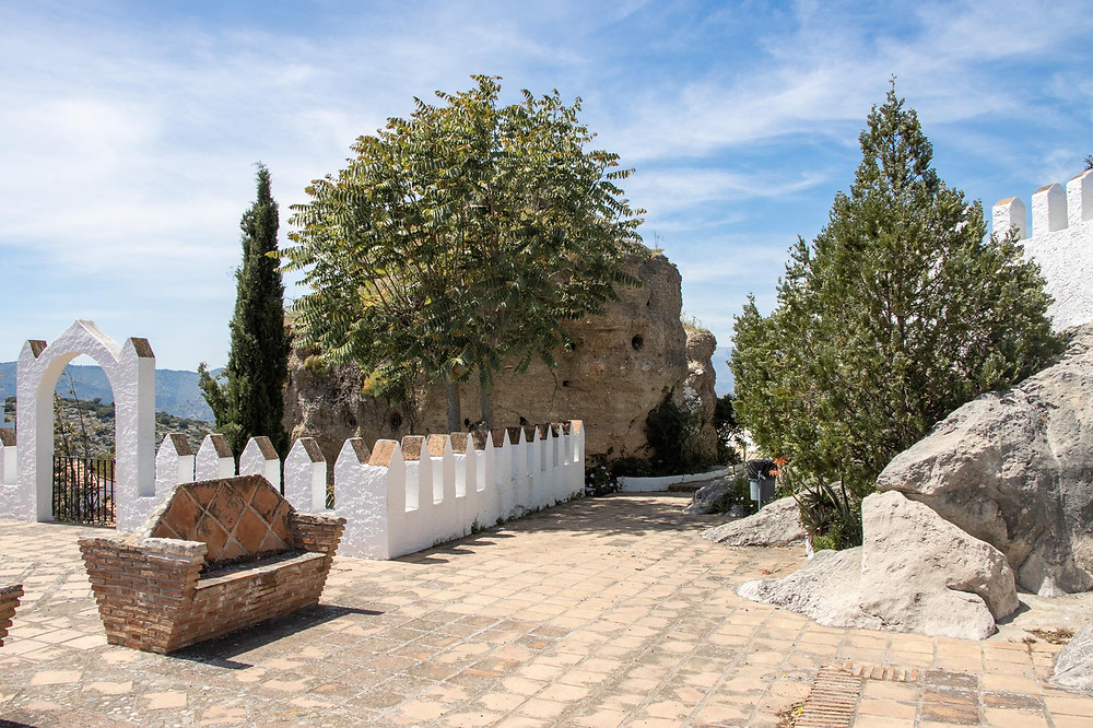View of a sitting area at a viewpoint with white walls and a small rounded castle tower in the background.