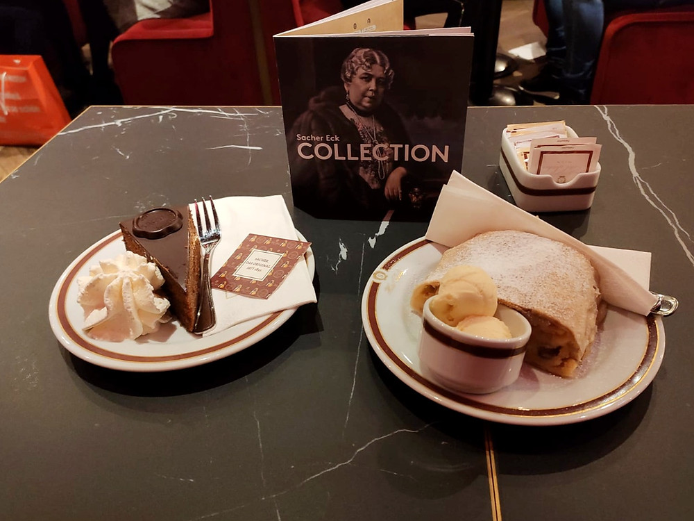 Black marble table with a plate of apple strudel and ice cream and another plate with a chocolate cake slice and cream.