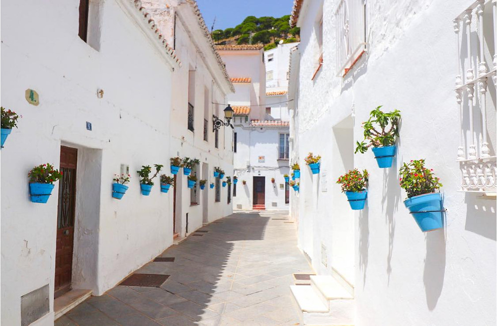 Narrow whitewashed street lined with blue plant pots.