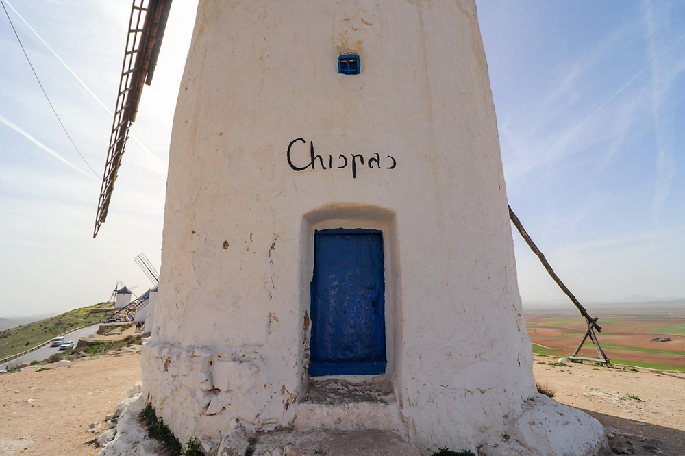 Close up of one of the white stone painted windmills with a bright blue door and a name painted at the top of the door in black.