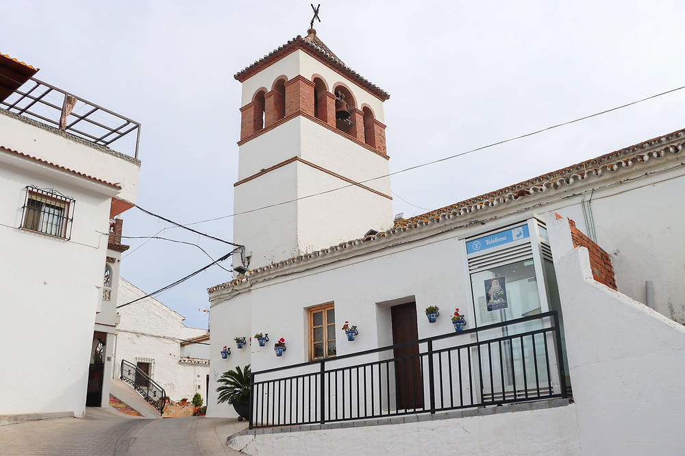 White buildings with a white tower in the centre that has brickwork around the top.