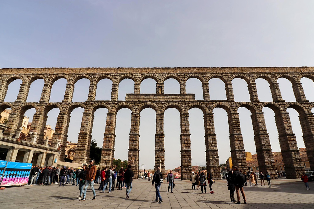 Roman aqueduct made up of tall arches running the length of the photo in a square in Segovia.