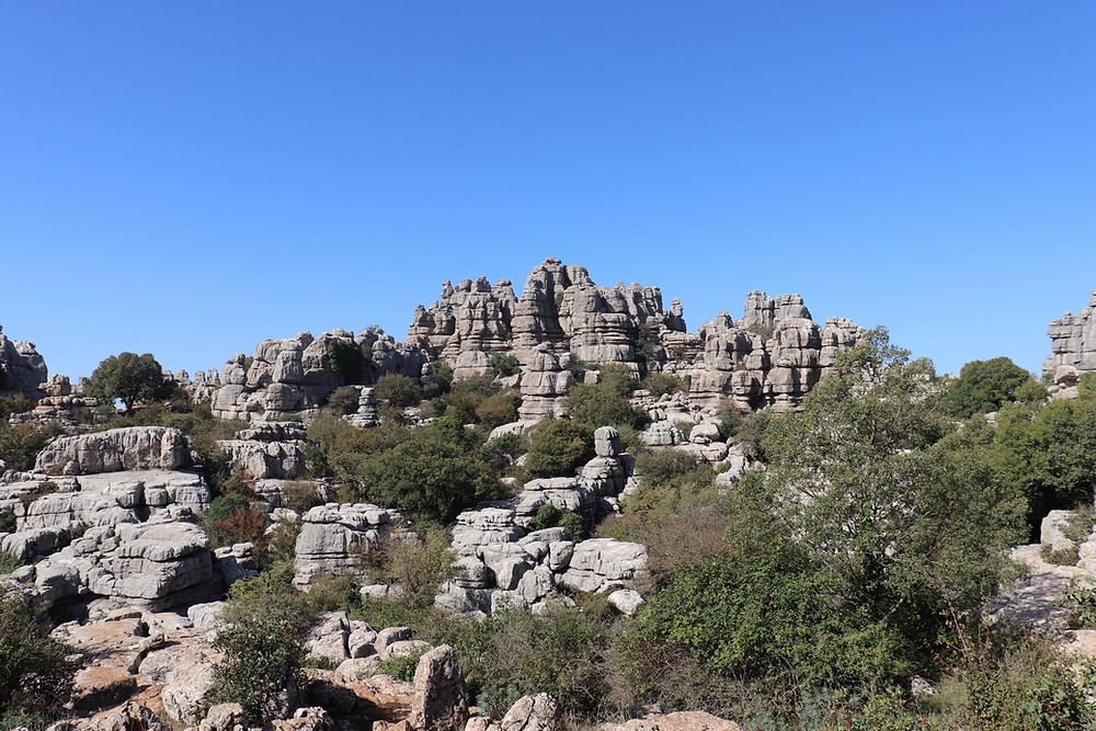 View of the stacked limestone rock formations in El Torcal de Antequera on a clear sunny day.