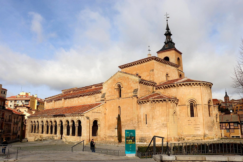 Romanesque style church in an orange brick with red tiled roof and a tall tower.