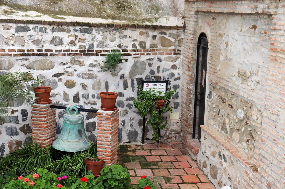 Entrance to the crypt inside the town church. A sign at the entrance is tiled and there is an iron bell sitting in some flowers.