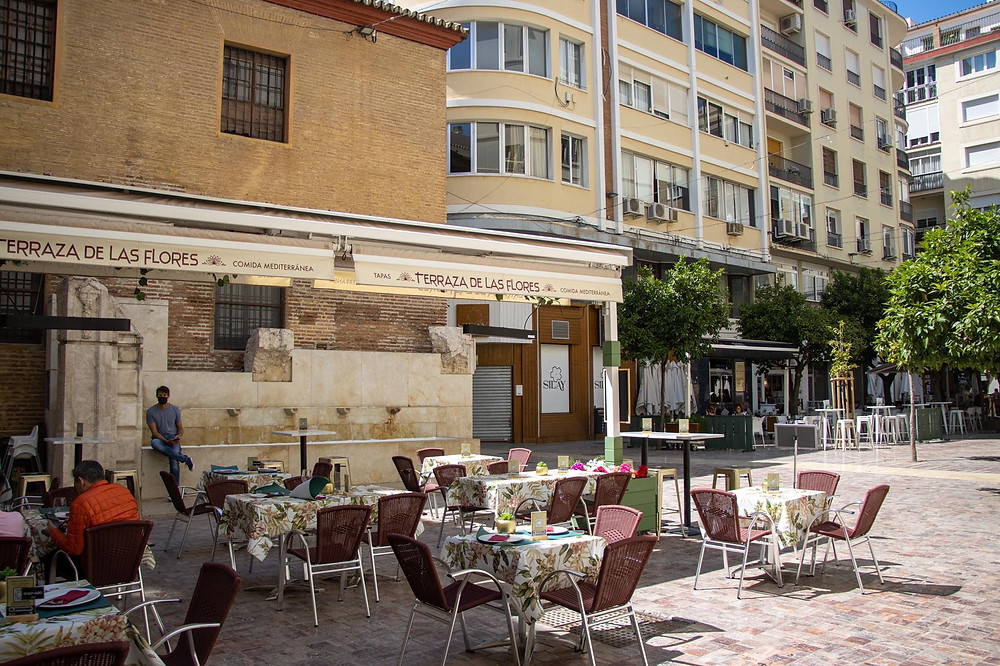 Small plaza surrounded by tall buildings in Málaga with a ruined Roman wall.