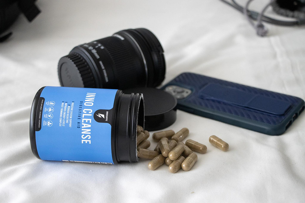 Pill container on the bed spilling out the supplements with a camera lens and phone in the background.