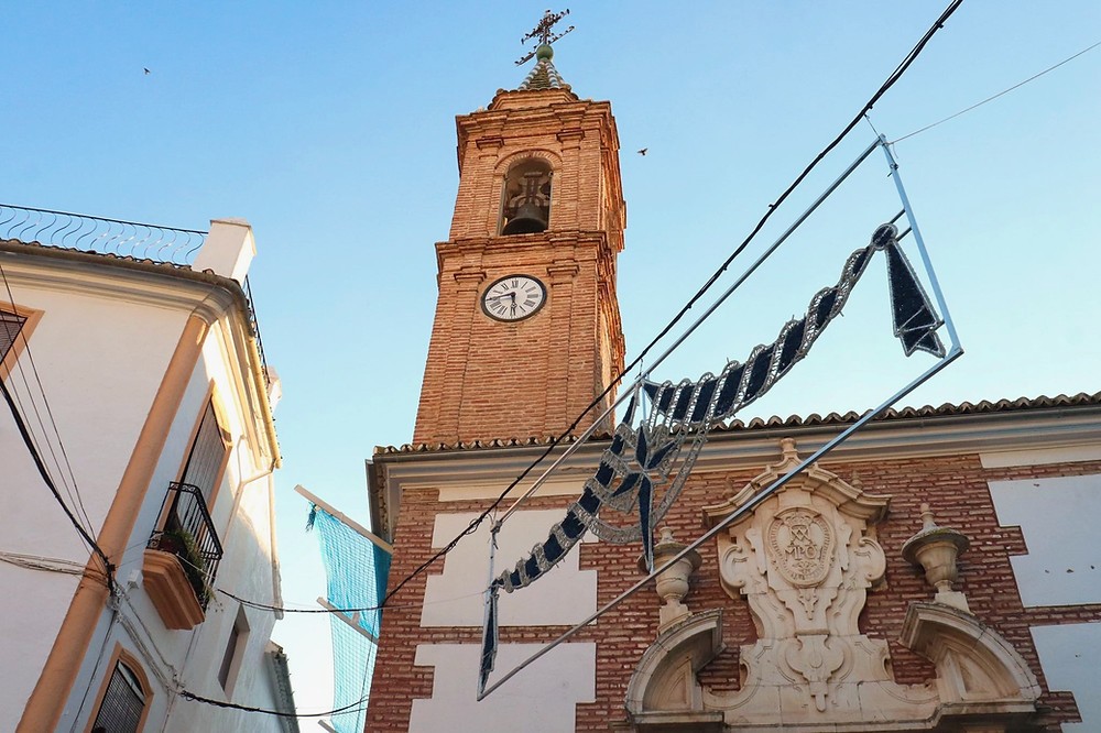 The bell tower of Iglesia de Jesús Nazareno against the backdrop of the bright blue sky in Archidona.
