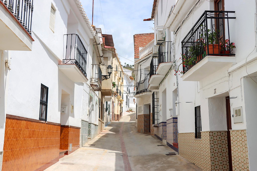 White washed street going up a hill with tall narrow buildings.