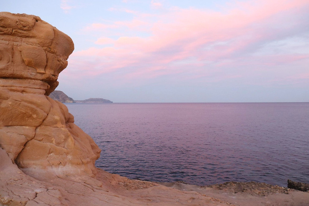 Pink sky at sunset, view from the rocks at Playa el Playazo in Almeria, Spain