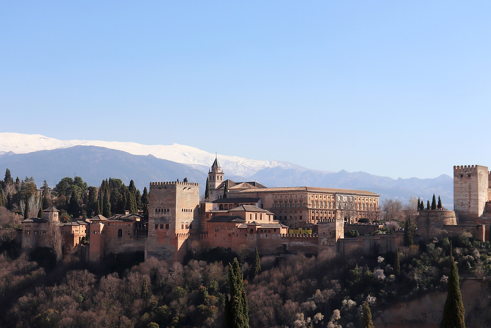 Mirador de San Nicolás view of the Alhambra and the Sierra Nevada mountains behind it in Granada, Spain