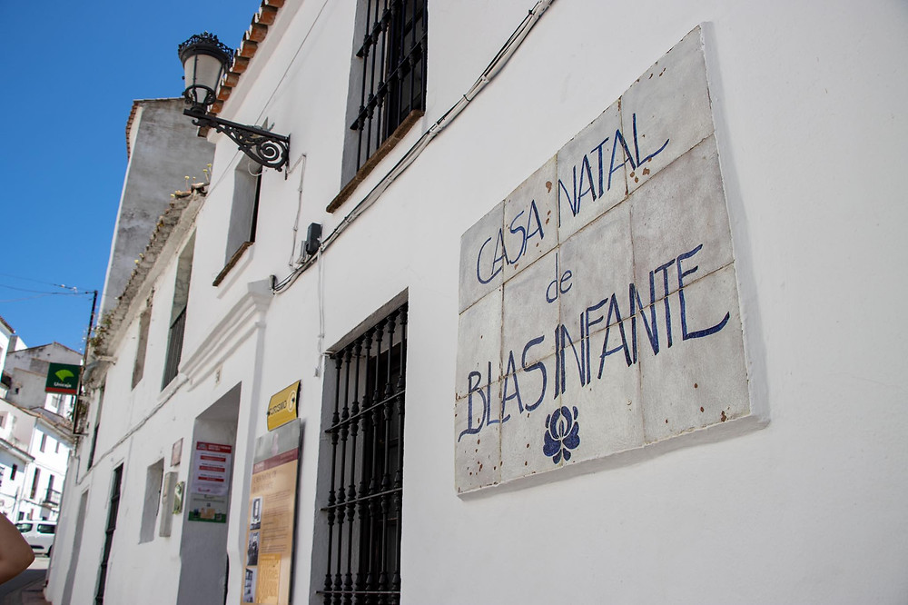 Sign on a white painted building from an angle reading Casa Museo de Blas Infante.