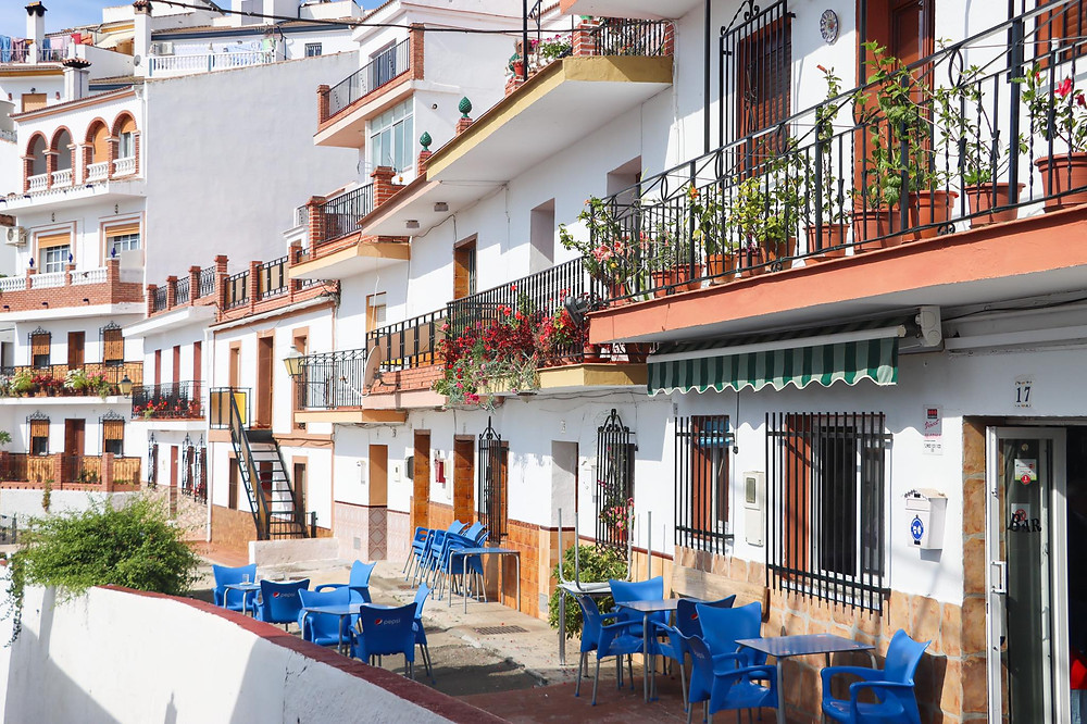 Row of white houses on multiple stories curving around a corner with blue chairs outside on a balcony.
