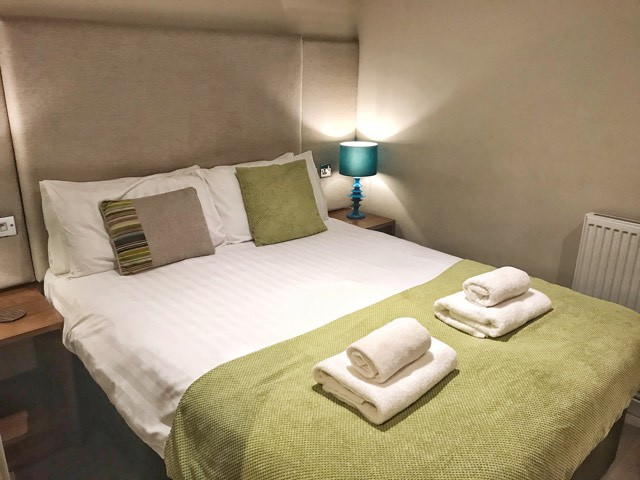 Double bedroom with folded towels in Base Serviced Apartments Chester, England