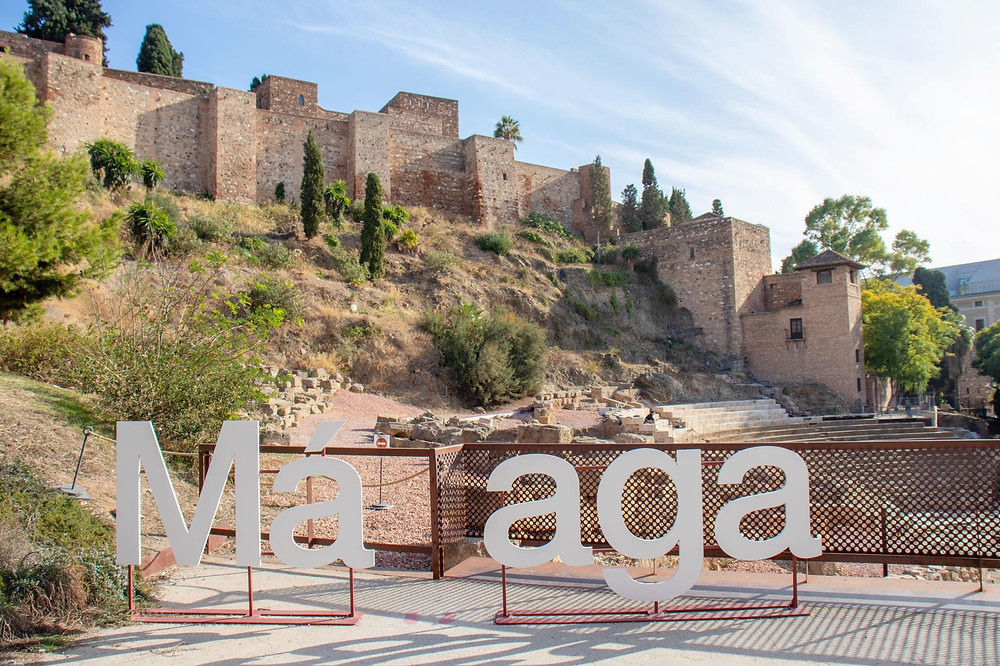 A white sign making up the word Malaga with individual letters, a space in the middle so the person can be the L. Behind it sits the fortress on the hill and the Roman theatre below.