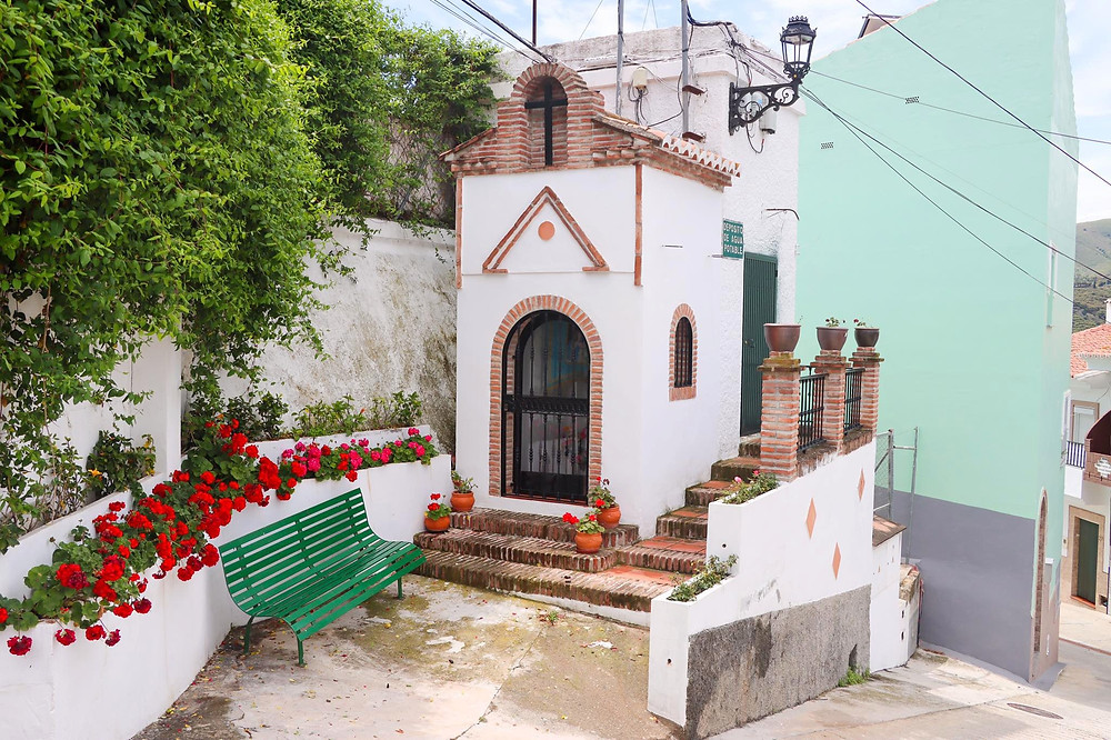 Small religious sanctuary set into a wall with a green bench beside it.
