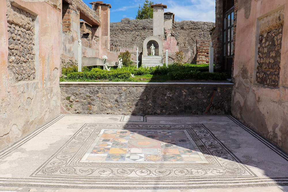 Inner courtyard of a house with a tiled floor with a garden in the background.