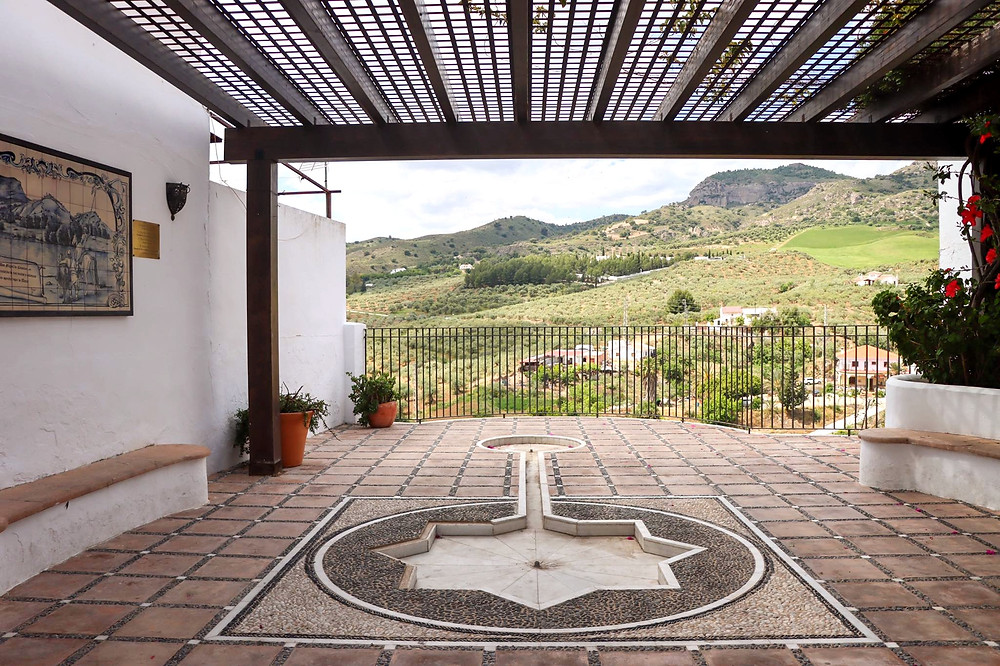 Viewpoint in the village of Álora which has a shaded cover over the top of it and a water feature turned off in the centre.