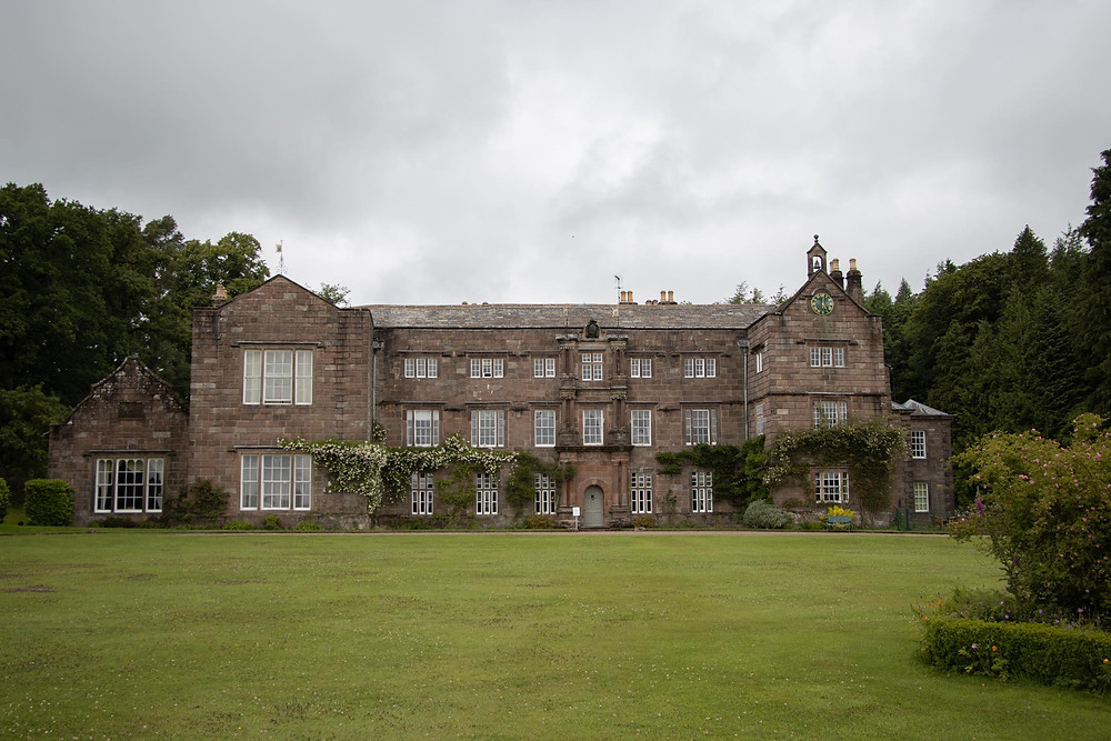 An old country house sitting in front of a large grass lawn with lots of windows in it.