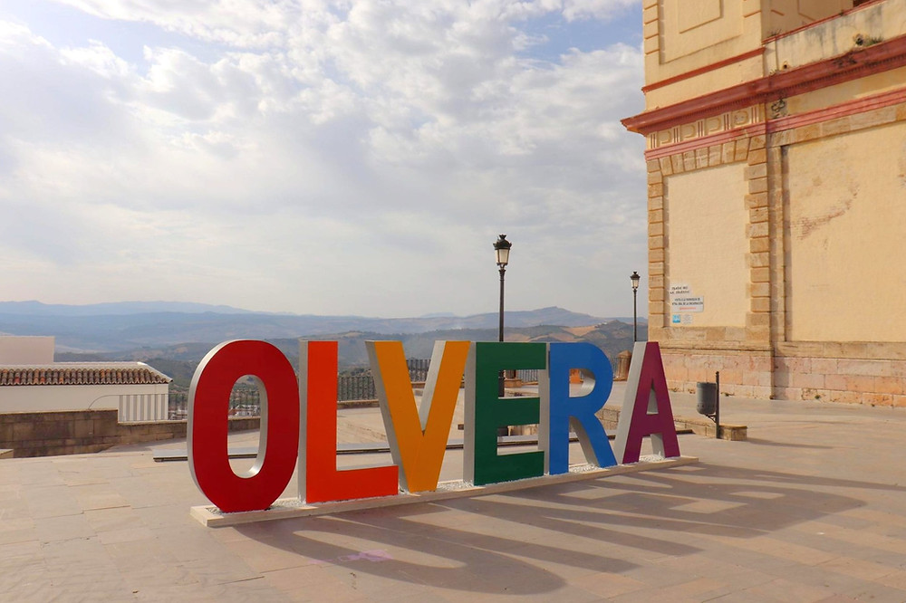 3D Olvera sign in multi-colour next to the church and the castle with views of the landscape, Spain