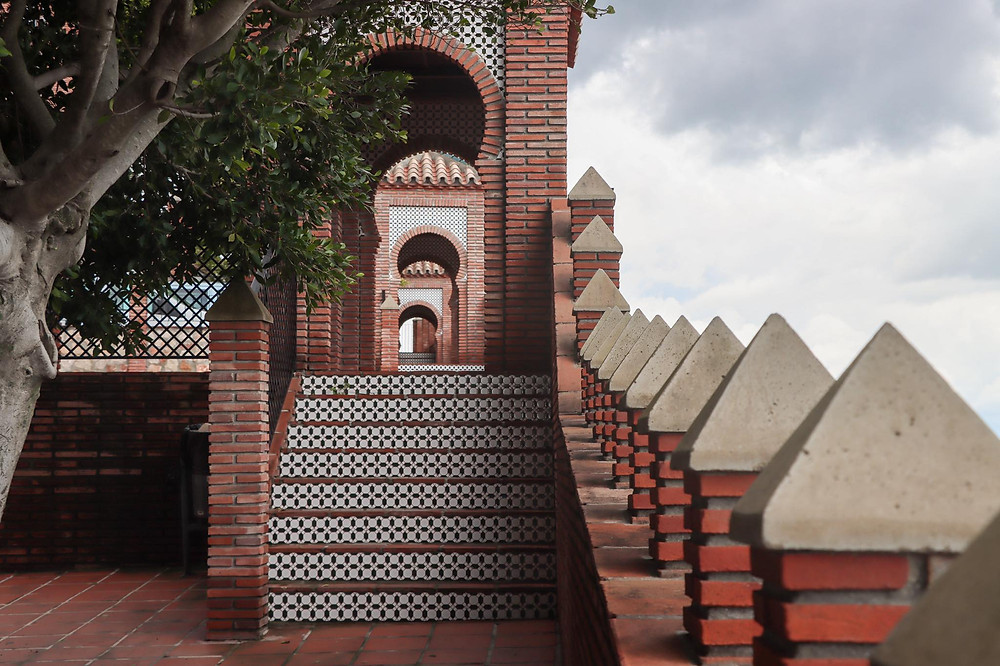 Row of Arab arches on the side of a viewpoint made of bricks.