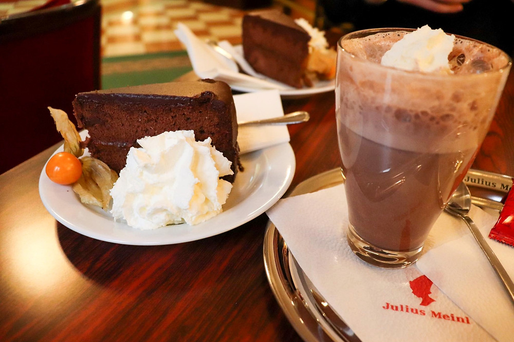 Sacher Torte/chocolate cake with cream and an orange tomato, a glass of hot chocolate with whipped cream sits next to it.