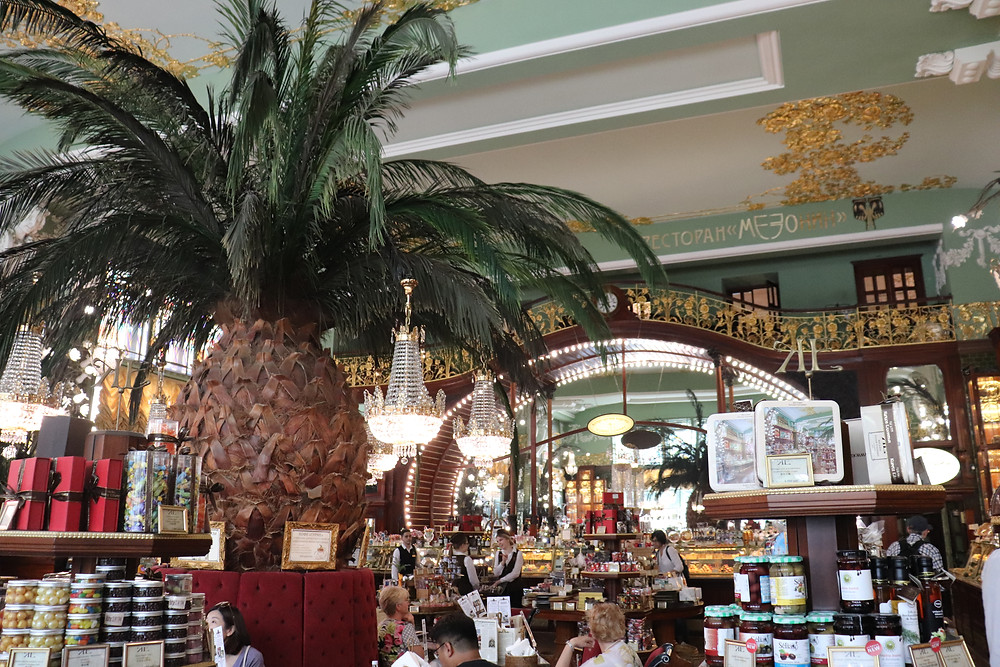 Inside the Eliseyev Emporium with a giant pineapple and displays of food st petersburg russia