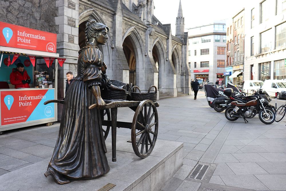 Statue of Molly Malone next to a church in Dublin Ireland