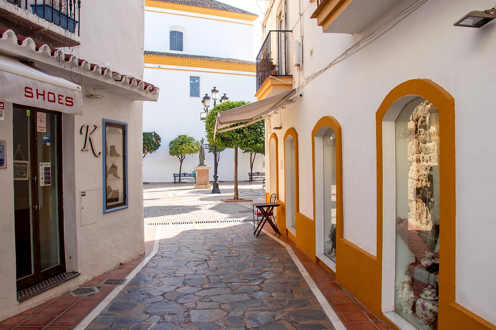 Narrow street with white washed buildings sitting in the shade, opening up into a larger plaza.