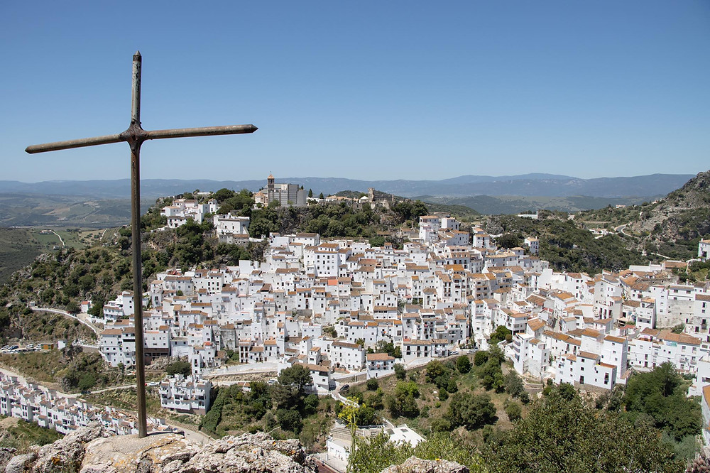 View of a white village spread across a hill with an iron cross in the frame of the viewpoint.