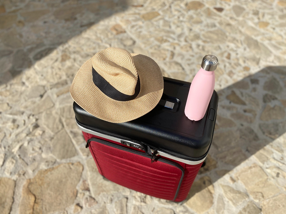 Hat and water bottle on top of the Pull Up Suitcase in Castillo de Castellar, Spain