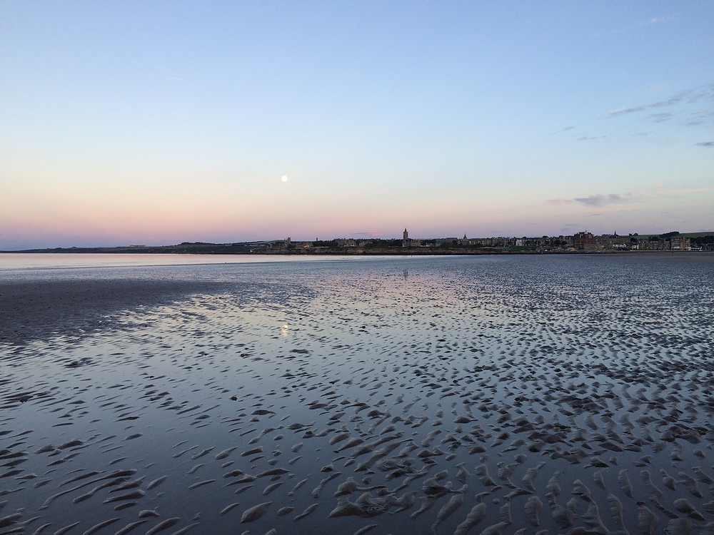 View of St Andrews coastline from West Sands at sunset in Scotland