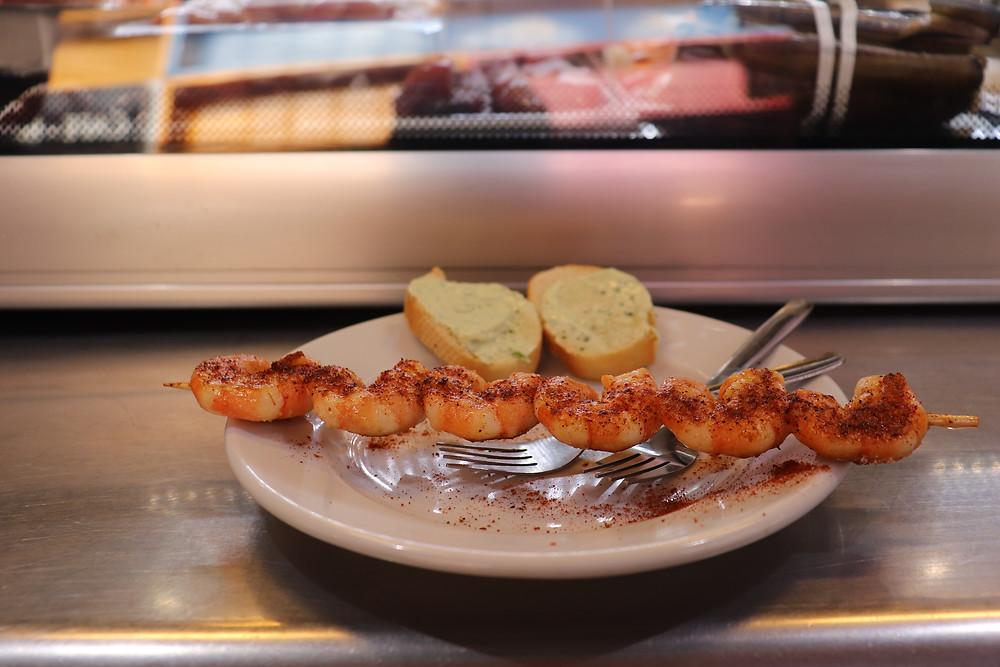 Grilled shrimps with seasoning on a kebab in Malaga market Spain