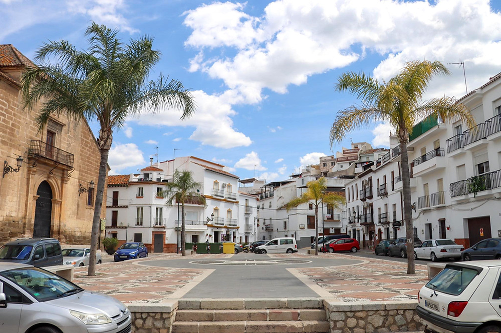 Small town square with palm trees on either side, white buildings surrounding it and a medieval church on the left.