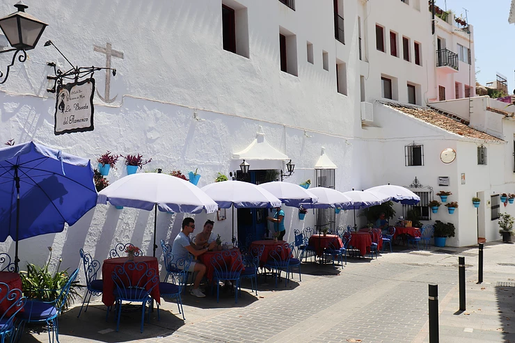 White washed building with blue plant pots on the wall and tables outside with blue umbrellas.
