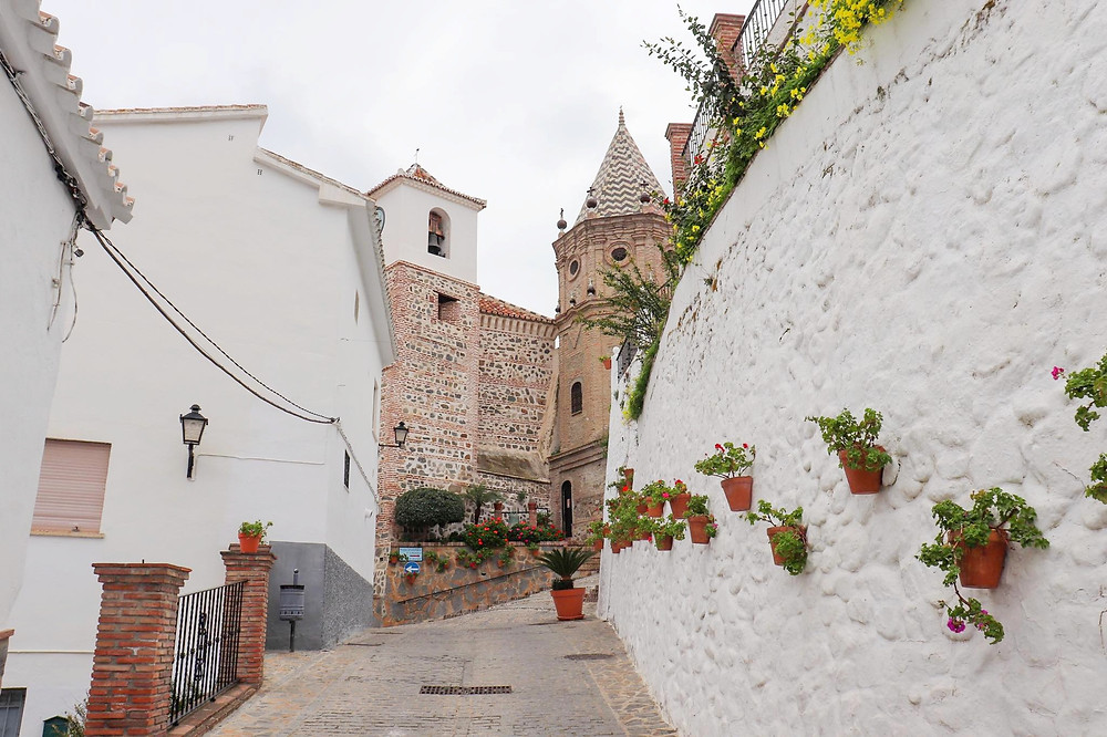 Curved pedestrian street with white walls and flower pots on the wall. An old church tower is at the end of the street.