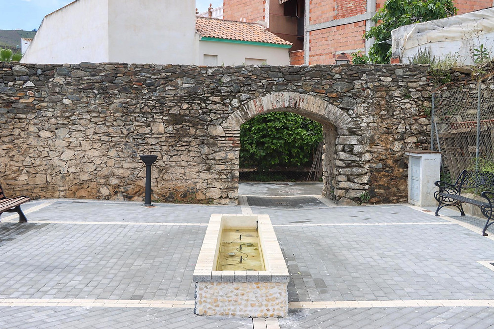 Small stone wall with an arch on the side of it sitting in a small plaza.