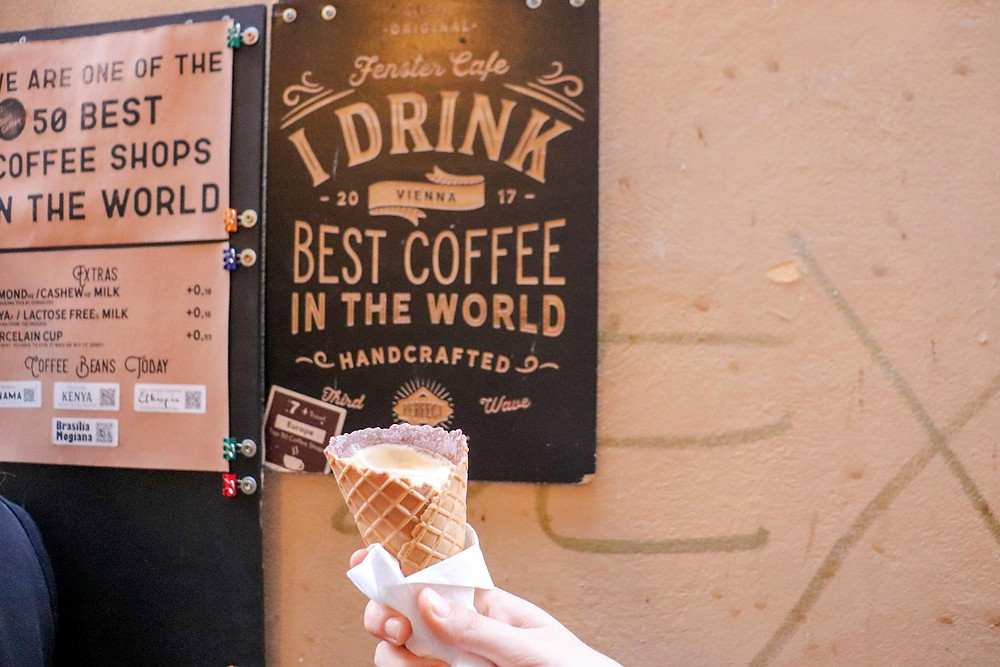 An ice cream cone filled with coffee being held in the air in front of the coffee shop sign.