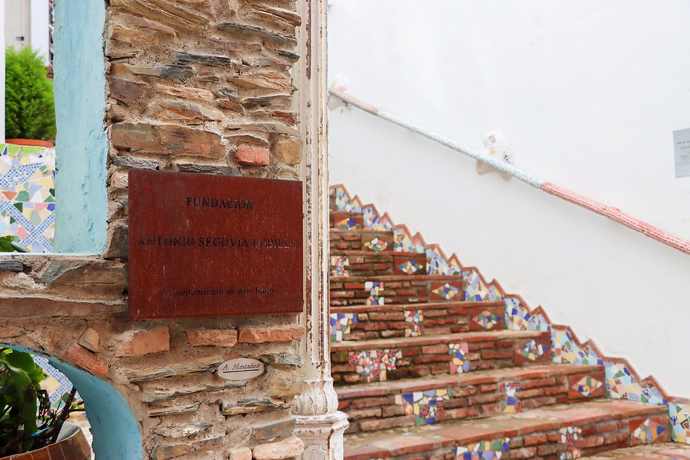 Rusted sign on a stone wall with steps in the background decorated in tiles.