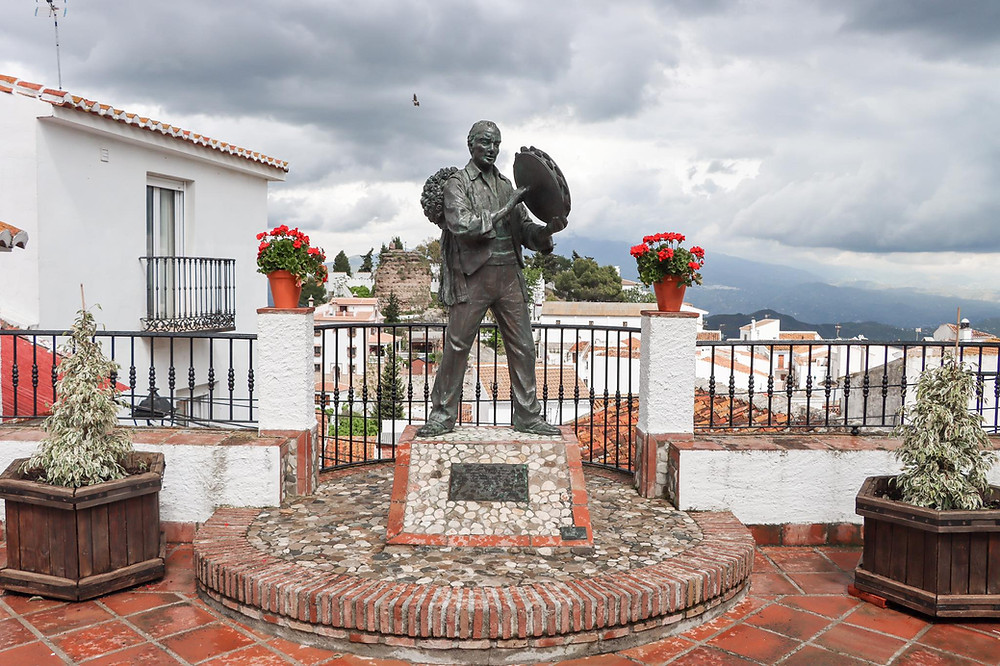 Statue of a man playing a tambourine on a platform made of small stones, overlooking white houses in the village.