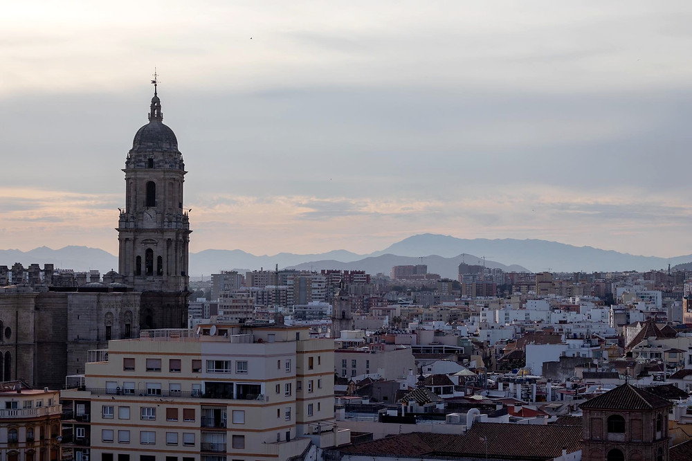 View of Malaga's cathedral and the city with mountains in the background from the top of the castle, the sun had just finished setting.