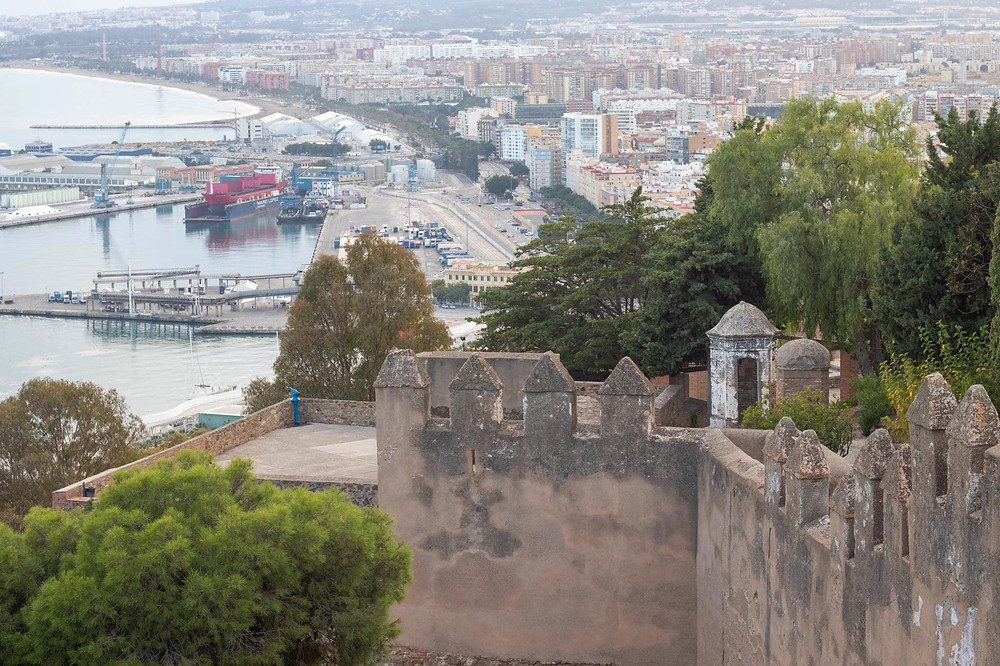 View of Malaga port and part of the city from the walls of the castle, sitting high on a hilltop with trees blocking some of the view.